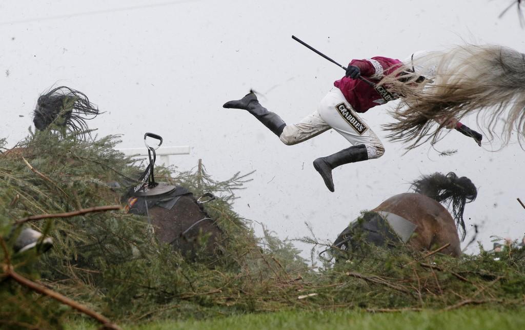 Sports - First Prize c Tom Jenkins, The Guardian, Grand National Steeplechase, World Press Photo 2017. Jockey Nina Canberry vliegt van haar paard Sir Des Champs tijdens de Grand National van 9 april 2016 in Liverpool. Een ander paard (On His Own, rechts) is enkele momenten daarvoor ook onderuit gegaan bij deze hindernis. De paarden en hun jockeys raakten niet gewond.