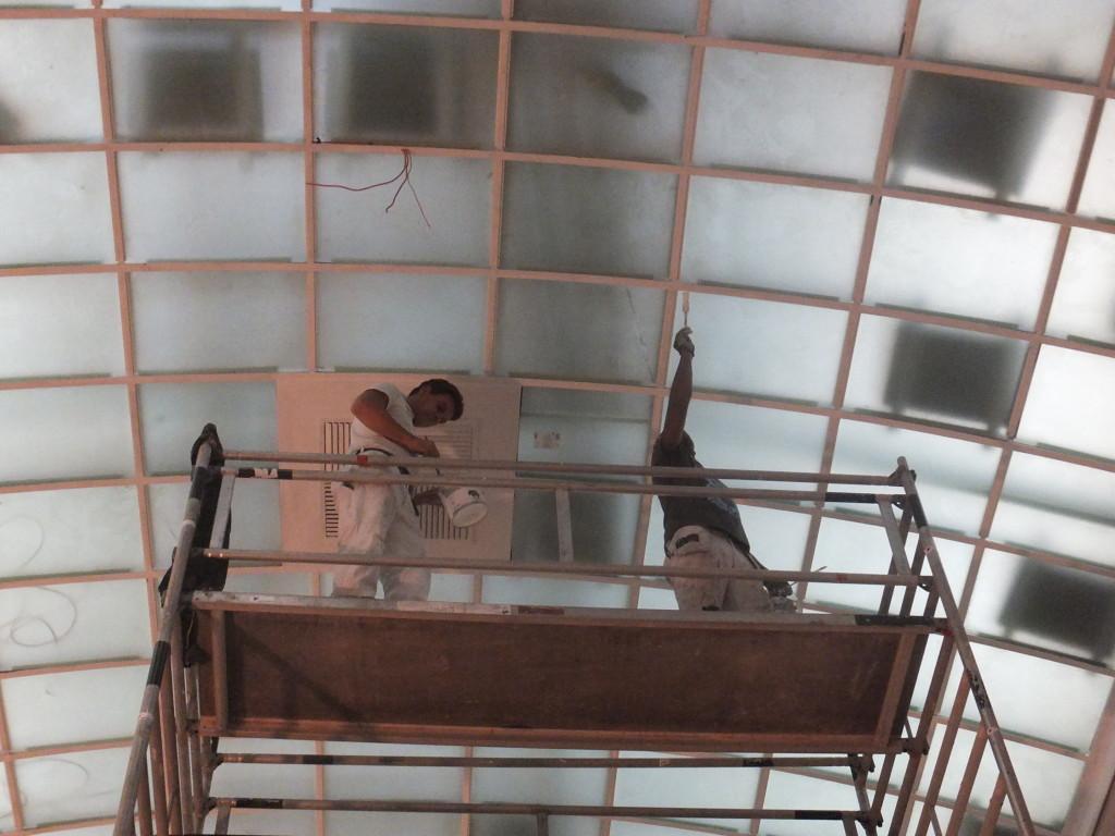 Schilders bezig met een opknapbeurt van een glazen overkapping van een van de tentoonstellingszalen. Eigen foto