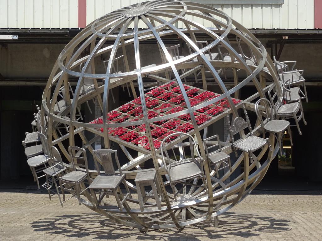 Chen Zen, Back to Fulness, Face to Emptiness. De metalen globe staat op de binnenplaats van De Meelfabriek. Hij is omringd door stoelen uit verschillende tijden en culturen, in het midden staat in het Chinees een samenvatting van de Universele Verklaring van de Rechten van de Mens. Eigen foto.
